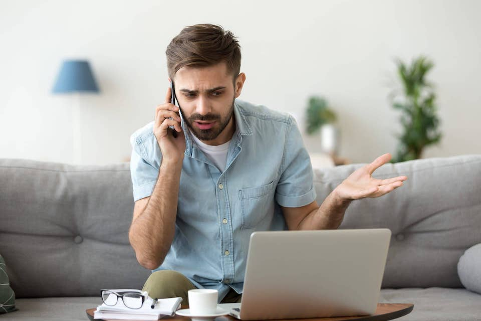 frustarted man on phone sitting on the couch with a laptop in front of him; diy roofing